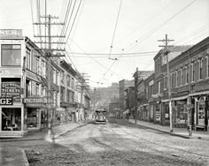 "August 1910. ""Main Street, Gloucester, Massachusetts."" The sidewalks and signage of a century ago."