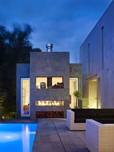 This modern stone home takes outdoor living to a whole new level with a sleek lap pool, spacious living area and fireplace. Design by Ilija Karlusic