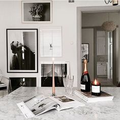 Decorator Arijana Heinrici has chosen her favorite photo art from Printler, the online marketplace for photo art. Gorgeous marble table with champagne bottle and candlestick in white modern home. https://printler.com/sv/