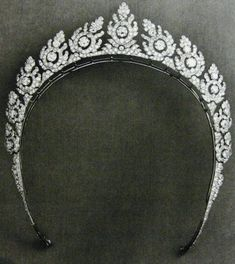 A delicate diamond 'halo' tiara, circa 1930, by Cartier. Featuring eleven stylised floral motifs, each with a large circular diamond at its centre.