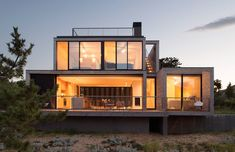 A beach house in the Hamptons with concrete framed spaces with walls of glass, expansive decks and a rooftop terrace. Click through for more images of this ultra-modern home.