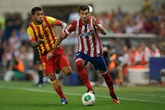 Leonardo Baptistao (R) of Atletico de Madrid competes for the ball with Dani Alves (L) of FC Barcelona during the Spanish Super Cup first leg match between Club Atletico de Madrid and FC Barcelona at Vicente Calderon Stadium on August 21, 2013 in Madrid, Spain.