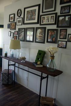 This console table was created by using a old piece of barn wood. Staining it a dark brown, and using galvanized pipes for the legs. This allowed the desired effect of a chic and rustic industrial table without spending a lot of money. The industrial console table compliments the softness of the rest of the space with white board and batten and light gray walls. A picture gallery wall finishes up the space nicely. Full tutorial is provided at http://www.ourhousenowahome.com/