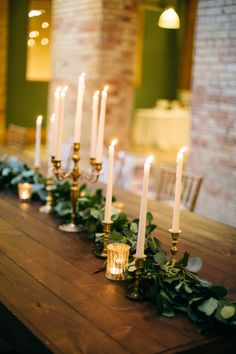 brass candlesticks with tall tapered pale pink candles, lined along the trestle tables among a bed of foliage and pink petals
