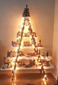 """Here's a lovely idea to do if you have an old ladder in the garage! Make a beautiful Christmas village with lights and houses! This was made by Lydia Mendoza. She says """"I had an old ladder from a yard sale. I put planks of wood that I painted white on the Christmas Tree Village, White Christmas Trees, Christmas Villages, Beautiful Christmas, Christmas Lights, Christmas Crafts, Christmas Ideas, Christmas Christmas, Christmas Traditions"""