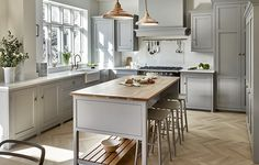 Surbiton kitchen design hand painted in Little Greene 'Lead' with bespoke cabinets, traditional fittings and modern appliances. Grey kitchen cabinets and light oak interior and island worksurface. Wooden parquet flooring and Carrara marble-effect composite worktops.