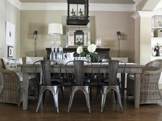 Reclaimed wood farmhouse table, wicker end chairs, industrial metal chairs, large latern light, neutral color scheme from HGTV