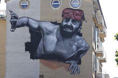 """MTO """"The Mediterranean Tunnel"""" - L'opera si compone di due murales, uno a Silema (Malta) e uno a Sapri in provincia di Salerno, che raffigurano un migrante con pantaloni rossi e ciabatte ai piedi che squarcia il muro di una casa per comparire a 700 chilometri di distanza  (da Muri per i migranti, gli street artist raccontano il dramma)"""