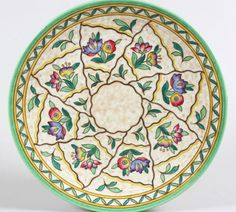 """Crown Ducal charger (c1939) """"Trellis""""   # 6016 pattern designed by Charlotte Rhead   Tube lined and decorated with pink and blue foliate sprays and green leaf sprigs within wavy edged panels, on a mottled ground, pattern no.6016, 43cm diameter, printed factory mark and facsimile signature   Sale Price £200-300   #charlotte_rhead"""