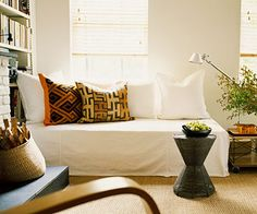 Twin bed turned couch with a drop cloth slip cover. Love the pillows and lamp too!