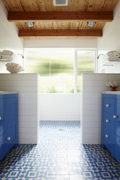 Bathroom with modern design and contrasting patterned tile floor. Love the double shower heads and exposed wood ceiling. - Design by Bestor Architecture