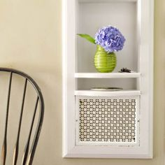 The old front-hall telephone nook, with a perforated metal panel to screen the ringer, retains its role as a conversation piece in a 1938 Colonial Revival home.