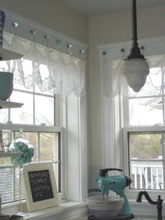 Glass knobs installed on the window frame make a way to hang curtains. Via Restyled Home.