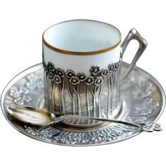 Silver and porcelain Art Nouveau coffee cup with holder, saucer and spoon. There is gold rim on the cup. Dainty floral detail in silver. Could be used as a teacup as well. Fine china porcelain antique cup.