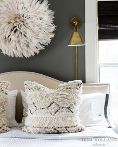 Gorgeous gray and ivory transitional bedroom boasts walls clad in dark gray paint holding an ivory juju hat above a cream camelback nailhead headboard lit by a wall mount brass swing arm sconce pointed down towards black and white bedding accented with ivory Moroccan wedding blanket pillows.