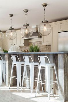 lovely white barstools with backs, and those three large glass globe lights are pretty neat!