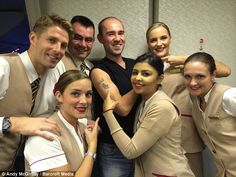 Glasgow-born teacher Andy McGinlay (centre) poses with cabin crew during one of his flights with Emirates. McGinlay has the luxury airline's logo tattooed on his arm.
