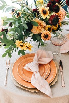 Small Space Entertaining An Early Fall Themed Tablescape with layered Anthropologie coral orange plates wooden chargers natural linen tablecloth knotted pink linen napkins rose gold flatware utensils and gold rimmed pink wine glasses.