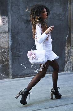 White sweater dress with black polka dot tights and spiked heals.