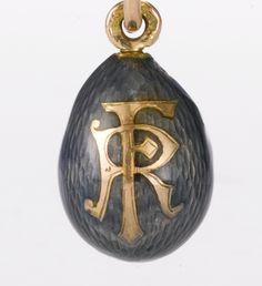A Russian gold and transparent enamel Easter egg pendant and varicolor gold bracelet, St. Petersburg the egg enameled steel grey over an engine-turned ground, engraved and set with the date 1901 and the Latin initials RF, maker's mark obscured. The initials RF probably stand for République Française; the egg was probably intended as a commemorative gift during the Imperial family's state visit to Dunkurque, Compiègne, Reims and Paris, France from September 18 to 21, 1901. (back)