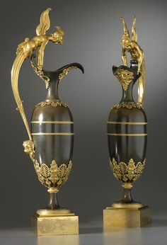Fine pair of Empire gilt and patinated bronze ewers attributed to Claude Galle, each of elongated baluster form mounted around the collar and base with stylized palmettes and acanthus leaves, the spout applied with a bearded male mask and balanced by a channelled and pearled scrolled handle supported on a putto mask and terminated above by a winged classical maiden clasping the rim, on a spreading circular domed foot on a square gilt bronze base  Paris, date circa 1810-15  Height 62 cm. each.