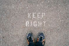 Looking down at my feet and a sign that reads KEEP RIGHT. by Lucas Saugen #fromwhereistand #keepright