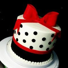 This pretty buttercream birthday cake features black polka dots and a red bow.   **Custom colors and ombre colors available at...