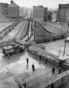 Восточногерманские полицейские убирают улицу (Генрих Гейне Штрассе) после строительства пропускного пункта 4 декабря 1961 г. Западный Берлин был окружен стеной протяженностью 155 километров. Вначале это была обычная стена из бетонных блоков высотой три с половиной метра, но вскоре она превратилась в мощный комплекс инженерных сооружений, состоявший из пяти линий заграждений общей шириной до 150 метров: эскарпы, рвы, контрэскарпы, стены, проволочные