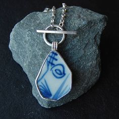 Unique pendant featuring a pottery shard that was found on the banks of the Thames in London, set in silver with a silver chainThis shard was such a pretty shape, that apart from a thorough cleaning, it is pretty much exactly how I found it. I have made a custom setting for it in fine and sterling silver, and it hangs off a diamond cut sterling silver chain. The clasp is part of the design - you wrap it round your neck and thread the toggle underneath the loop to close it. The weight of the…