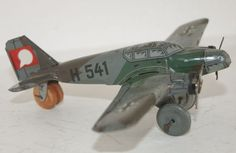 Hammerer & Kühlwein Germany - Lengte 14 cm - Blikken Vliegtuig H-541 in militaire uitvoering jaren 40  Een echt en origineel gemaakt in Duitsland periode 1938/'40. Vanwege de aanwezigheid van een Swastika zijn enkele foto's retoucheerd.Blik speelgoed Oorlogsvliegtuig Heinkel H - 541Afm.ca.Span; 18cm - Wings;135cm - gewicht ca.; 60gr.Materiaal; BlikConditie; goede staatHet achterwieltje is van licht balsa-hout en misschien niet origineelBekijk aub goed mijn foto's;Ze zijn een correcte…