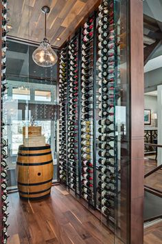 Don't hide your wine cellar... highlight it! Make it a see-through showcase like this one made of glass and walnut wood planks.