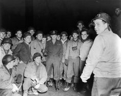 5th February 1945: Full-length image of General Dwight D Eisenhower, Supreme Allied Commander, standing outdoors amongst a group of soldiers at night, World War II. (Photo by Anthony Potter Collection/Getty Images)
