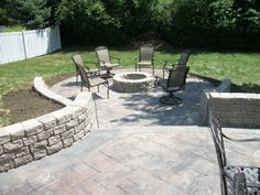 Stamped concrete patio with retaining walls and fire pit in matching stone