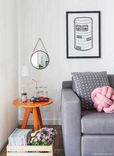 Sala de estar tem sofá cinza, móveis de madeira e muitos objetos com estilo escandinavo.