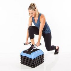 Grab a pair of dumbbells and stand behind a step. Place right foot flat on the center of the step and lower down into a squat, holding weights in front of shoulders, palms facing in.