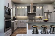 Designer Jordan Iverson creates a polished look in this open-concept kitchen with durable quartz countertops and Shaker-style cabinets painted a soft gray for a new take on the classic.