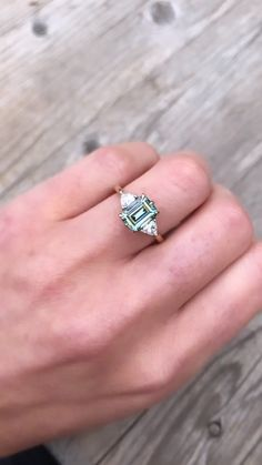 A three stone ring featuring a rare emerald cut Teal Iconic Moissanite, with lab-grown trillion cut side diamonds. Set in a handcrafted recycled gold setting. Green Engagement Rings, Green Sapphire Engagement Ring, Diamond Wedding Rings, Vintage Engagement Rings, Emerald Cut Rings, Aquamarine Rings, Emerald Cut Sapphire Ring, Saphire Ring, Emerald Cut Moissanite