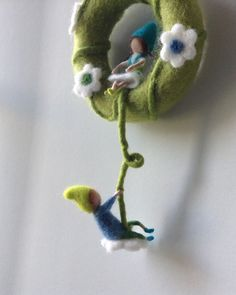 A mobile with two little needle felted pixies on a hoop. The pixies are made of 100% merinowool. The hoop is covered with wool. The diameter of the