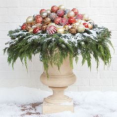 Watch Martha Stewart embellish a pair of urns with ornaments and greenery to flank outdoor walkways this winter.
