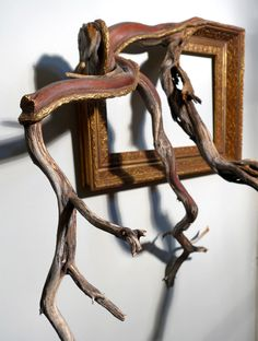 Artist Darryl Cox fuses ornate vintage picture frames with tree branches found in the forests of central Oregon. The branches serve as a simple reminder of the materials used to build picture frames, but also create an unusual form factor where clean lines and ornate moulding patterns seem to natura