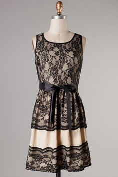 http://www.gabbyroseboutique.com/sleeveless-babydoll-dress-with-black-lace-patterning-outer-layer-and-tie-ribbon-on-the-waist-96-polyester-4-spandex-contrast-100-nylon/