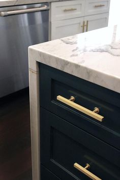 Gorgeous blue gray kitchen island drawers painted Benjamin Moore Stonecutter are accented with a brass t-bar pulls and a Macauba Quartzite waterfall countertop.