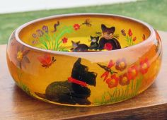 Carved Bakelite bangle with Scottie, cats, and flowers  Apple Juice is the color of the bracelet