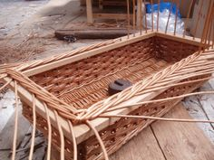The wooden frame here is being woven into the basket.  Holes need to be drilled all around the frame and the willow uprights inserted through and then bordered down.  This is an alternative to dropping the finished basket into a frame.
