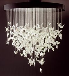 Many white butterflies tied to a circle creating a chandelier Possible ideas would be stars and circles or big and little hearts. and metallic paper or paint!