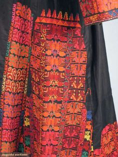 Palestinian woman's dress and shawl, black cotton dress w/ dense, stunning cross-stitch embroidery in red, pink, orange, yellow, white, & green, black silk damask shawl w/ embroidery similar to dress, early 20th c