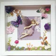 Fairy Art Frame  A beautiful fairy picture brought to life with 3D detailing. A genuine porcelain Dezine fairy in a flower petal dress of lilacs and purple, flutters beside a pretty butterfly in a spring country garden.  The fairy frame is decorated with moss, artificial flowers, a sparkling glass jar of magic fairy dust and tiny little ladybird.  My fairy garden frames are all one of a kind so you can have your own piece of Whispering Wood fairy magic on display, knowing it is completely…