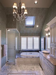 Designer Tina Muller placed one wall of the shower enclosure on the tub deck. The floors are Calcutta gold marble and cabinets are painted creamy white with a warm glaze. From Dreamy Tubs and Showers