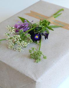 Natúr csomagolópapír, pár szál virág dekortapasszal rögzítve az ajándékcsomagoláson = tökéletes egyedi ajándék.