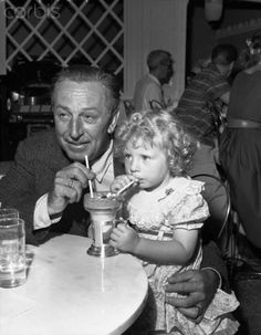 Original caption: First visitor to Disneyland in Anaheim, California, sneaked in one day early and got some special treatment from the big bossman. She's Elaine Long, 3, and her host for an old-fashioned ice cream delight in Carnation's Gay Nineties ice cream parlor was no other than Walt Disney himself, the man behind the $17-million entertainment park.